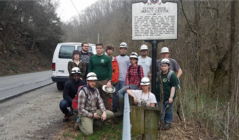 Group photo of Geology students near the Flynn Impact Crater information sign, which is located west of Cookeville, TN