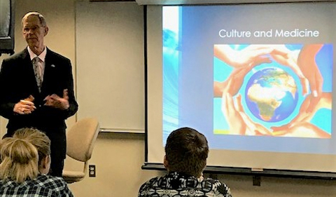 Dr. John Brose, Dean Emeritus of OU-HCOM, discusses Culture and Medicine with pre-med students. Shown here in front of screen.