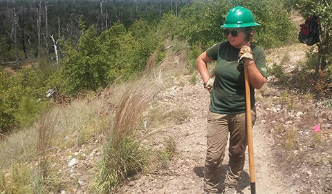 Taylor Major-Dame, in green hard hat and sunglasses, paused during clearing of backpacking trail in Bastrop State Park, Texas.