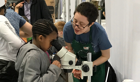 Ava Heller helps a schoolchild use a microscope.