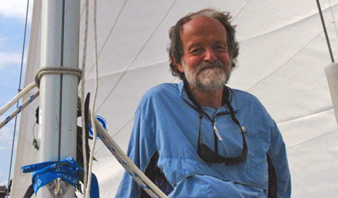 A smiling Gene Ammarell with sailboat sail behind him, mast to his side
