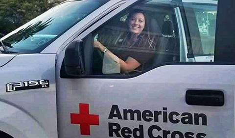 a smiling Kelsie Geyer behind the wheel of F150 with American Red Cross logo on truck door