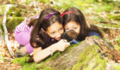 Young explorers in forest using a magnifying glass and studying mushrooms