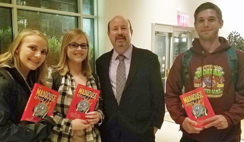 Students, from left, Krista Thomason, Becca Steinberg and Zachary Matthews pose with books signed by author Michael Mann.