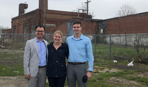 Bowen Shi, Ellenore Holbrook, and Jarrett Quanrud at the Mosaic Tile (brownfield) site. Group photo with factory in the background.