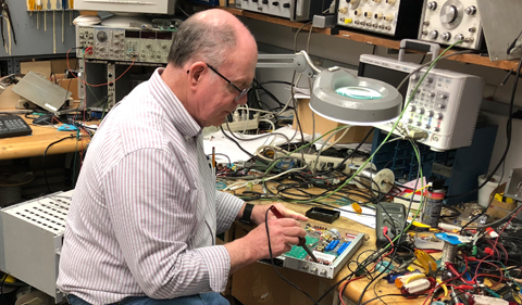 Don Carter repairs a high voltage module for use in powering a particle detector at the Edwards Accelerator Lab.