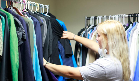 Woman looks at clothes on ranks in the Career Closet.