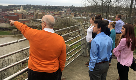 Zanesville Community Development Director Jay Bennett speaks and points to things with geography students about the city.