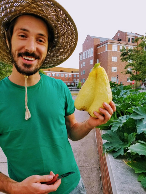 Benjamin Shonk holding two yellow squash.