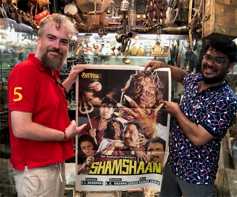 Dr. Brian Collins holds a horror film poster from India.