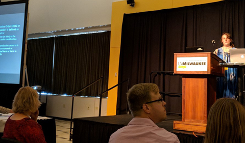 Danielle D'Amore presents at the conference, shown here at lectern.
