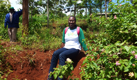 Edna Wangui in the field, shown here sitting on a dirt ledge.