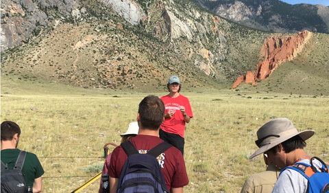 a tall man wearing a red shirt, black shorts, and a green hat is facing the camera. Students wearing backpacks and field gear face him with their backs to the camera. The backdrop is a mountain area with exposed geology in Montana