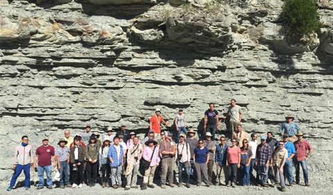 a group photo of adult men and women all in various outdoor wear standing in front of a rock cliff