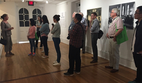 a group of adult men and women listening to a woman speak while standing in a museum with art displayed on the walls