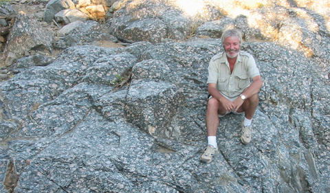 a white man with gray hair and a gray bear smiles as he sits on a collection of rocks in the sun