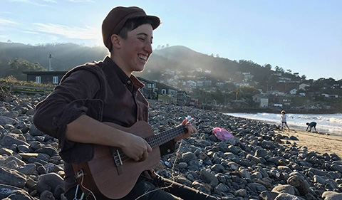 A smiling Seed Minkin sitting on a rocky beach with houses in the distance while strumming on a ukulele