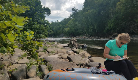 a white female writing in a notebook is sitting on rocks along the Greenbrier River