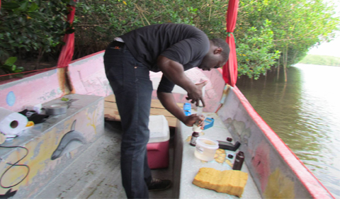 Abioudun Emmanuel Ayo-Bali, a geological sciences graduate student from Nigeria transfers a water sample from a syringe into a collection bottle while standing in a metal boat. He is surrounded by various research supplies and is facing away from the camera.
