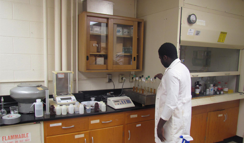 Abioudun Emmanuel Ayo-Bali, a graduate student from Nigeria stands in front of a collection of sample tubes sitting on a counter that is full of various analysis equipment. He is a lab coat facing away from the camera.