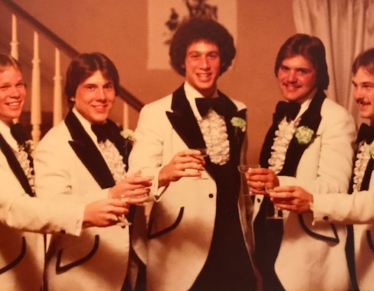 Five men stand together, wearing tuxes, holding champagne glasses