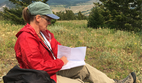 a dark haired woman wearing glasses and a green ballcap with a dark red jacket and khaki pants sits in a field of scrub grass reviewing a map folded in her lap. The background is a mixture of hills and valleys of Montana.