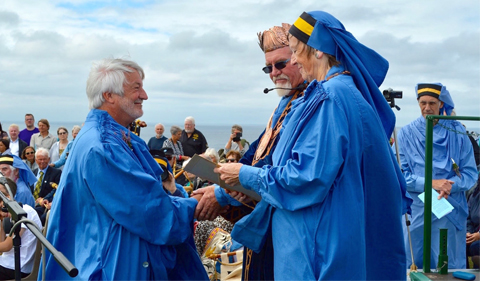 R. Damian Nance shakes hands with a male colleague while receiving a certificate from a female colleague, all dressed in blue garb, at an outdoor ceremony seaside. The sky is filled with flully white clouds.