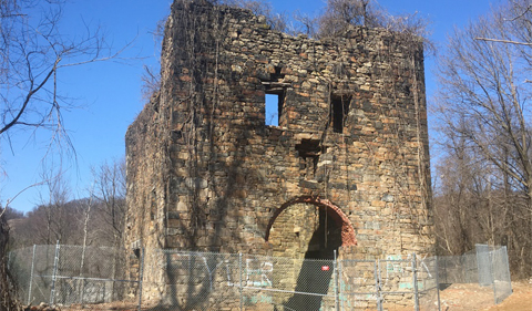 What remains of a stone building that used to house a steam pumping engine are surrounded by a chain link fence against a cloudless blue sky.
