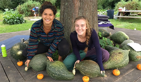Ange Heese and Lydia Beardsley pose for a picture, surrounded by recently harvested hubbard squash and mini pumpkins, in the circle gardens at the OHIO Student Farm.