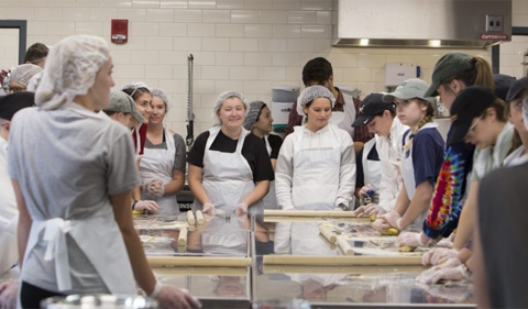 Students, dressed in aprons and hair nets, surround the working tables in the kitchen, and knead their pasta dough.