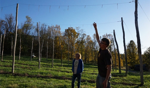 Steve Geisler stands with Casey Buchanan, who points as he describes how hops are grown.