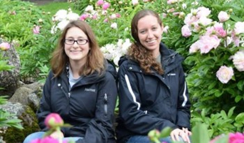 From left, Jen Bauer and Adriane Lam, sitting among flowers