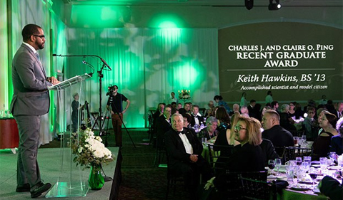 Keith Hawkins, BS '13, addresses those at the Alumni Awards Gala after receiving the 2018 Charles J. and Claire O. Ping Recent Graduate Award, shown here standing at lectern.