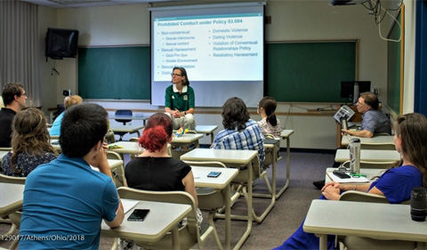 Standing at front of small classroom, Kerri Griffin presents Sexual Misconduct training at Linguistics Colloquium.