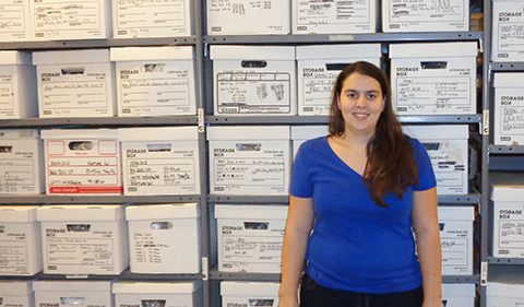 A smiling Rachel Meyer standing in front of file boxes