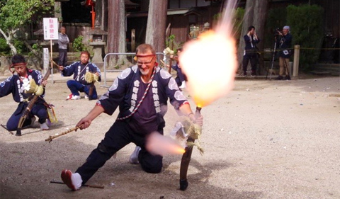 Thompson firing his assigned flintlock musket at Asuke Hachimangū Shrine on the first day of the Asuke Fall Matsuri, with the flash from the musket clearly visible.