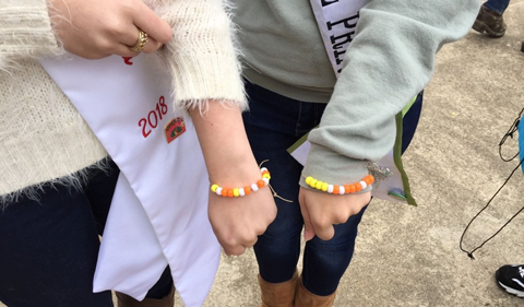 Two arms with yellow and orange bracelets.
