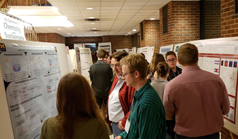OHIO Chemistry & Biochemistry graduate student Eli Skelton and Professor Michael Jensen talking with a poster presenter about their research.