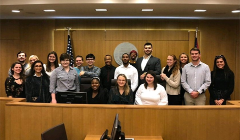 Members of Phi Alpha Delta pose in the Moot Courtroom at Cleveland-Marshall College of Law