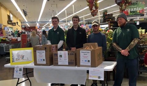 Nicholas Snider, Steven Weinstein, Kyle Bussard, and Peter Hein at the Kroger donation station, shown standing in front of a table with boxes to collect food.