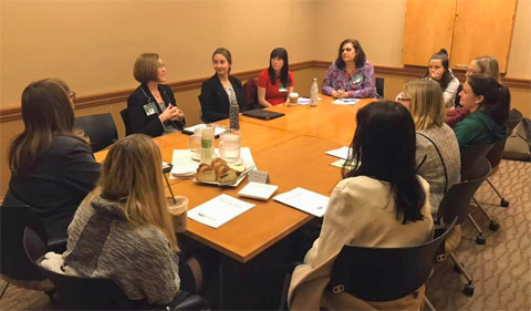 Students attend a Women in the Law panel with alumni, shown here seated around a table.