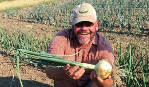 Mac Burgess, in field holding a vegatable.