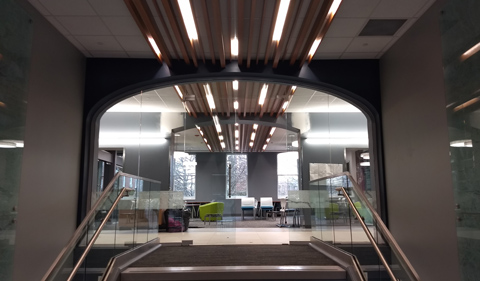 New entryway in Ellis Hall , with lighted ceiling beams and stairs going up to student collaborative space.