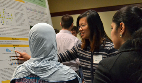 Doctoral student Yuan Zhang presenting her research to MCB graduate students Sazan Ismael and Dasmeet Kaur.