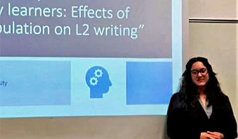 Carla Consolini presenting at SLRF, shown here with her poster.