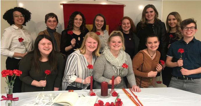 Photo of the new initiates of Sigma Delta Pi with their initiation roses.