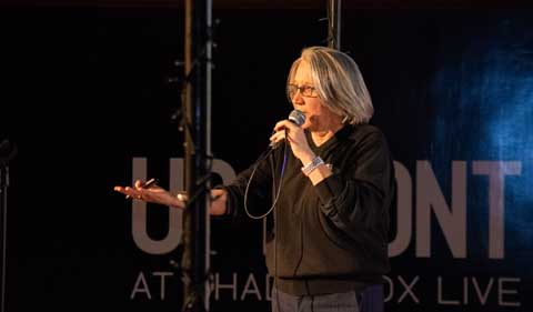 Sarah Wyatt at Columbus Science Pub, standing at microphone