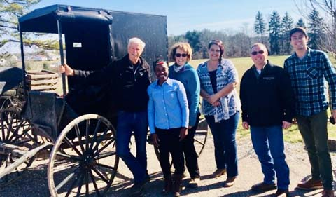 Margaret Gatonye conducted several farm visits together with the Rural Action team to understand and learn from the Amish growers, group shown here standing beside buggy.