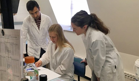 From left, Subhodip Adhicary (TBS graduate student), Samantha Selhorst (HTC Neuroscience student), Dr. Corinne Nielsen (Assistant Professor, Biological Sciences), shown at lab desk