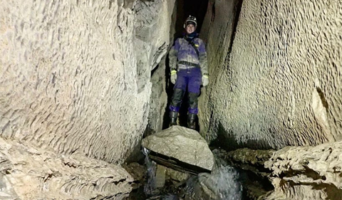 Lydia Albright, graduate student in Geological Sciences, standing atop a rock perched between two walls of a cave with water rushing around the rock
